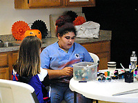 Marc Hayot/Siloam Sunday. Aavah Duncan gets ready to paint a young member's face at the Boys and Girls Club Halloween party.
