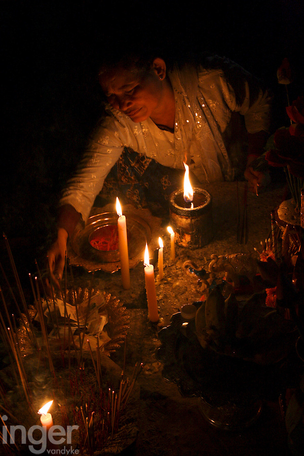 Woman lighting candles and incense inside Angkor Thom temple, Cambodia