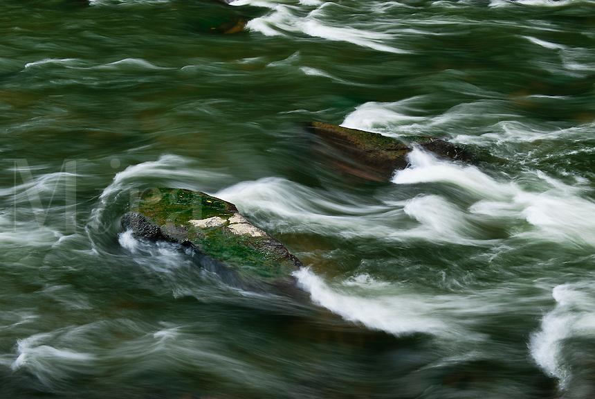 Rushing river flows around rocks.