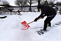 SNOW ROUND 2<br />Gloria Sommers (right) and her husband, Ron, both 80, shovel their driveway on Wednesday Feb. 17 2021  in the Larue community on Beaver Lake in east Benton County after another round of snow. The couple planned to spread play sand mixed with epsom salt on the drive after shoveling. The Sommers measured about 4 inches of snow at their home. Go to nwaonline.com/210218Daily/ to see more photos.<br />(NWA Democrat-Gazette/Flip Putthoff)