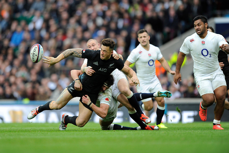 Sonny Bill Williams of New Zealand offloads as he is tackled by Tom Wood and Mike Brown of England during the QBE International match between England and New Zealand at Twickenham Stadium on Saturday 8th November 2014 (Photo by Rob Munro)