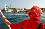 Istanbul, Turkey. Turkish woman on a ferryboat looking towards the docks. The Yeni Cami (New Mosque) was completed in 1663. Located next to the Spice Bazaar and Galata bridge is one of the best-known sights of Istanbul.