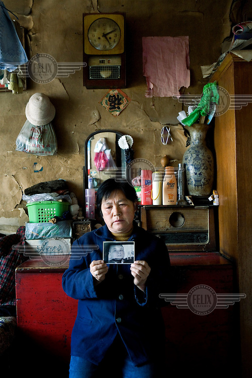 57-year-old Fu Yu Ru holds up a photograph of her son, Guo Qiang. Her son has been in jail for over a decade waiting for his death sentence to be carried out following a confession that he made while under torture. Fu Yu Ru believes that the court proceedings and evidence surrounding the case to be suspect and has been petitioning for an investigation into her son's conviction.