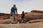 Father and son hikking on slickrock sandstone in Arches National Park, Utah, USA. .  John offers private photo tours in Arches National Park and throughout Utah and Colorado. Year-round.