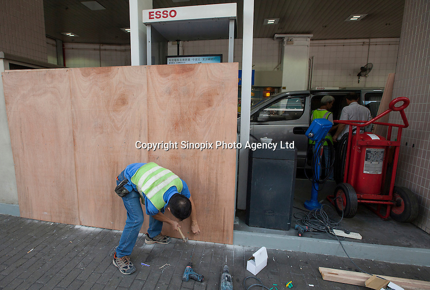 A worker employed by Esso boards up a gas station next to Hong Kong Police Headquartes on day three of the mass civil disobedience campaign Occupy Central, Wan Chai, Hong Kong, China, 30 September 2014.