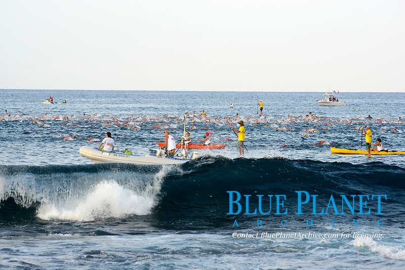 wave breaks with swimmers behind, kayaker, stand up paddleboard, boat, volunteer helping at the Ironman Triathlon World Championship Kailua Kona, Hawaii, Big Island, Pacific Ocean