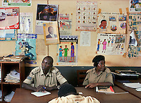 At the Department of Community Policing in the Jinja Police HQ, Corporal of the Family Protection Unit Peter Lokinomoi (L) and Constable Basemera Saudah (R) offer counseling to a man who is involved in a case of domestic violence with his mother.
