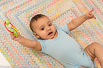 Infant boy age 6 months on back closeup waving rattle he holds