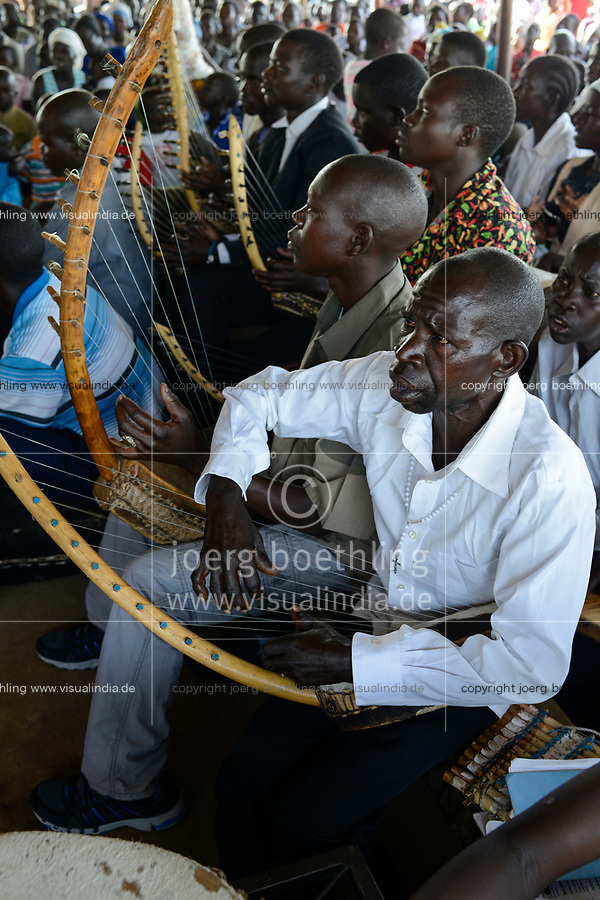 UGANDA, Arua, holy mass on sunday, musician play Enanga string instrument, trough zither / Sonntagsmesse in Dorfkirche, Kirchenmusik mit Ennanga Saiteninstrument aehnlich einer Zither