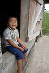 A Mayan boy sits in the window of his house in the Mayan community of San Miguel, Toledo, Belize
