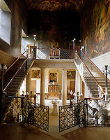 The Hall Staircase at Burghley House features a gated cantilevered staircase. The ceiling was painted by Antonio Verrio in the 18th century and the walls a century later by Thomas Stothard