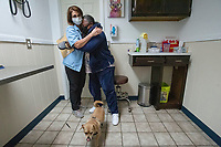 Dr. Kate Williams hugs veteran Cheryl Dotson (right) of Fayetteville at St. Francis Animal Hospital in Springdale after Williams examined Drake,, Dotson's service dog. Drake. The checkup and vaccinations from the visit were paid for by Bo's Blessings, a non-profit organized with the purpose of improving the quality of life and positively impacting the lives of the Northwest Arkansas military community. Visit nwaonline.com/210408Daily/ and nwadg.com/photos. (NWA Democrat-Gazette/J.T. Wampler)