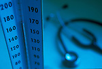 close-up of mercury rising on gauge on sphygmomanometer, stethoscope in background