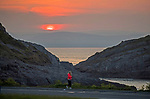 Swansea, UK, 24th April 2020.<br />An early morning walker watches as the sun rises over the Mumbles headland near Swansea today as government warnings continue to ask people to stay at home due to the Coronavirus outbreak that is spreading across the UK and the world.