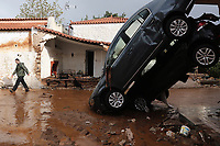 Pictured: Two cars sit almost upright against a house wall.<br />