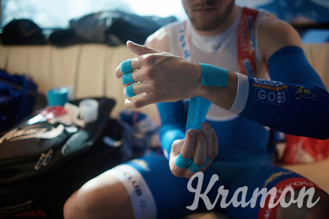 """Tim De Troyer (BEL/Wanty-Groupe Gobert) prepping himself ahead of the race in the teambus. <br /> The almost 53km's of riding over cobbles is so hard for the body that riders need to tape wrists and fingers to protect them. Most riders also have an extra layer of bartape on their handlebars to """"soften"""" the impact of the cobbles.<br /> <br /> 113th Paris-Roubaix 2015"""