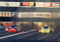 Nov 9, 2013; Pomona, CA, USA; NHRA funny car driver Jeff Arend (right) races alongside Gary Densham during qualifying for the Auto Club Finals at Auto Club Raceway at Pomona. Mandatory Credit: Mark J. Rebilas-