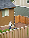 Grace Circle, Happy Valley, Oregon. Residential fence. Mowing lawn in backyard with an electric lawn mower.