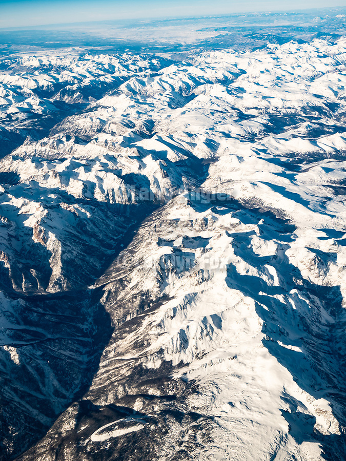 Colorado's San Juan Mountains with snow in winter during a window seat on a United Airlines flight from Chicago to Los Angeles over America's Flyover County.