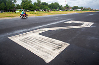 A motorbike rides along the main runway in central Funafuti. The runway makes up a large part of the central island and is sometimes used by locals for moving from one end of the island to the other. Located in the South West Pacific Ocean, Tuvalu is the world's 4th smallest country and is one of the most vulnerable to climate change impacts including sea level rise, drought and extreme weather events. Tuvalu - March, 2019.