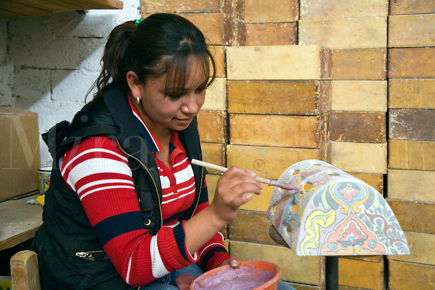 TALEVERA pottery is hand painted with glazes before firing in a workshop in the state of Guanajuato - DOLORES HIDALGO, MEXICO