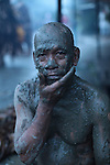 "A man covers himself in mud during the annual Taong Putik, or ""mud people,"" festival in Bibiclat, on Luzon island, Philippines. The festival honors St. John the Baptist, the village's patron saint, and devotees cover themselves with mud and dress in cloaks made from banana leaves and vines which symbolize the animal skins the saint wore in the Bible.  June 24, 2011."