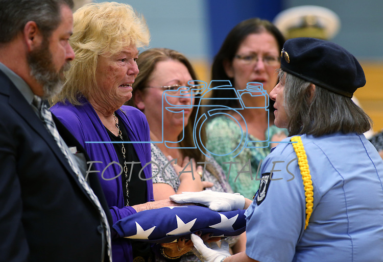 Peggy Eddington-Smith receives an American flag in her father's honor during a ceremony, in Dayton, Nev., on Saturday, Sept. 20, 2013. After 14 years of searching for relatives of World War II Private John F. Eddington, Donna Gregory, right center, returned his purple heart medal and other personal items to Eddington-Smith. <br /> Photo by Cathleen Allison/Las Vegas Review-Journal