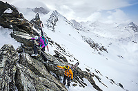 Two skiers with their skis on their packs, climb through rocks to access the descent route from the Tracuit Hut, Zinal, Switzerland.