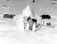 Sergt. (or T4c.) Marvin E. Eans, Jr., demonstrates the new snow cape being used by First U.S. Army Infantrymen in snow-covered areas in Belgium.  White rags are wrapped around his rifle for additional camouflage. St. Vith. December 15, 1944. T5c. Richard A. Massenge. (Army)<br /> NARA FILE #:  111-SC-197455<br /> WAR & CONFLICT BOOK #:  1069