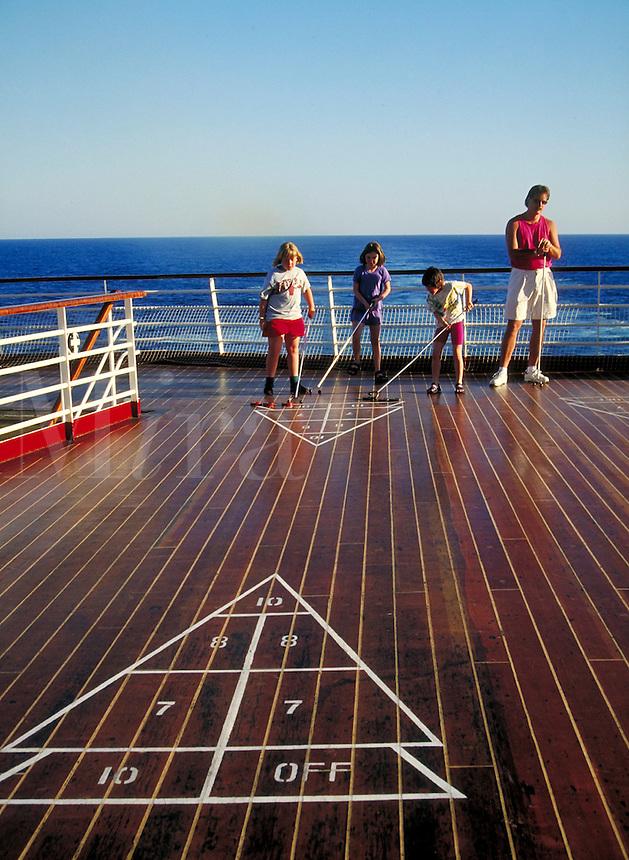 "children playing shuffleboard on board ""Song of America"" cruise ship deck. children."
