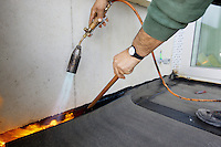 Switzerland. Geneva. A roofer worker from the company Cerutti Toitures SA is installing roofing felt with heat using a torch and flame (gas blowpipe torch) to waterproof the roof surface on a balcony. 18.03.14 © 2014 Didier Ruef