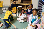 Preschool 3-5 year olds play gender typical group of boys playing with vehicles two girls in dressup playing with dolls horizontal