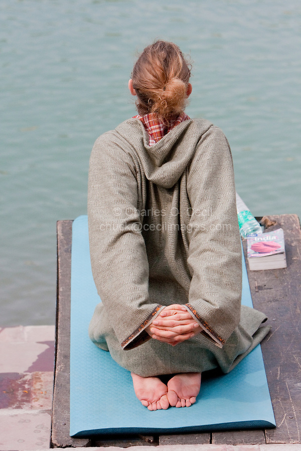 India, Rishikesh.  Yoga Practitioner Exercising on the Banks of the Ganges (Ganga).