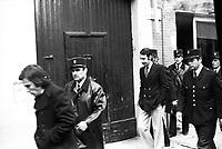 """Picard, Me Cathala, Me Bouscatel, Me Rastoul"""". Rue d'Aubuisson. 30 novembre 1976. Vue d'ensemble des accusés quittant la maison du docteur Claude Birague : José Picard (devant de profil) suivi de Christian Portay, sont entourés de policiers. Cliché pris le jour d'une reconstitution judiciaire dans le cadre de l'affaire du meurtre de René Trouvé. Observation: Affaire René Trouvé-Birague : le 19 février 1976, le journaliste René Trouvé est assassiné d'une balle dans la tête, par deux inconnus, alors qu'il regagne son domicile au 33 rue Bayard."""