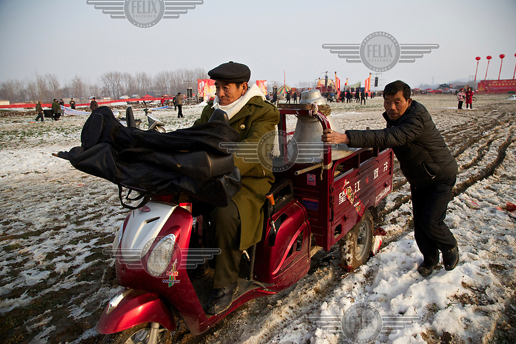 A traditional storyteller packs up his equipment at the Ma Jie folk festival. <br /> <br /> For centuries farmers in Henan have gathered during Chinese New Year in the region's wheat fields to listen to bards singing and recounting old tales. <br /> <br /> Now storytellers come from all over China to attend the annual festival where large crowds gather to watch the best performers.