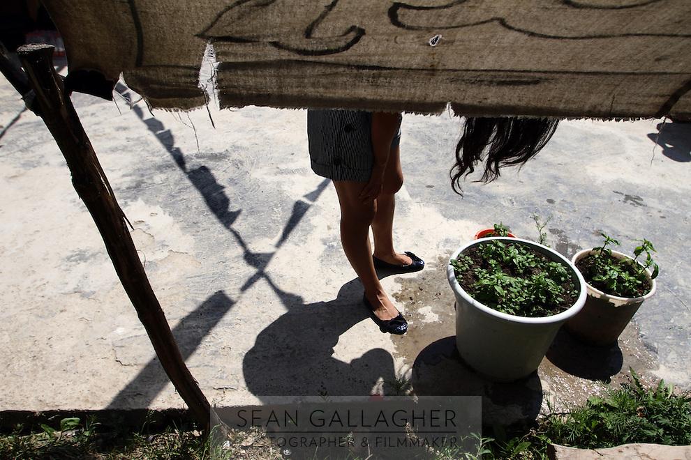A Tibetan woman washes her hair outside of her home near the Jiuzhaigou National Park. Sichuan Province. China.
