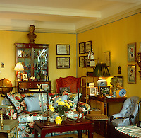 The cosy iving room is full of a variety of period furnitureand collections of artwork and china displayed in cabinets and on the walls