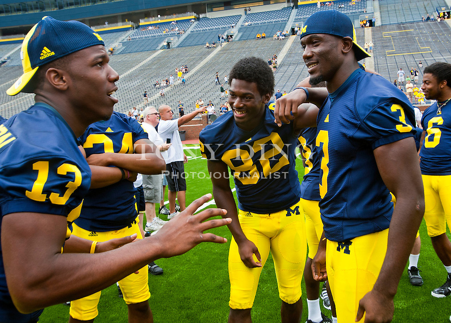 Michigan safety Carvin Johnson (13) jokes with wide receiver Ricardo Miller (82) and safety Marvin Robinson (3), at the annual NCAA college football media day, Sunday, Aug. 22, 2010, in Ann Arbor, Mich. (AP Photo/Tony Ding)