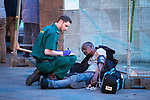 © Joel Goodman - 07973 332324 . 07/04/2017 . Manchester , UK . A paramedic tends to a man slumped on the ground in Piccadilly Gardens . Greater Manchester Police have authorised dispersal powers and say they will ban people from the city centre for 48 hours , this evening (7th April 2017) , in order to tackle alcohol and spice abuse . Photo credit : Joel Goodman