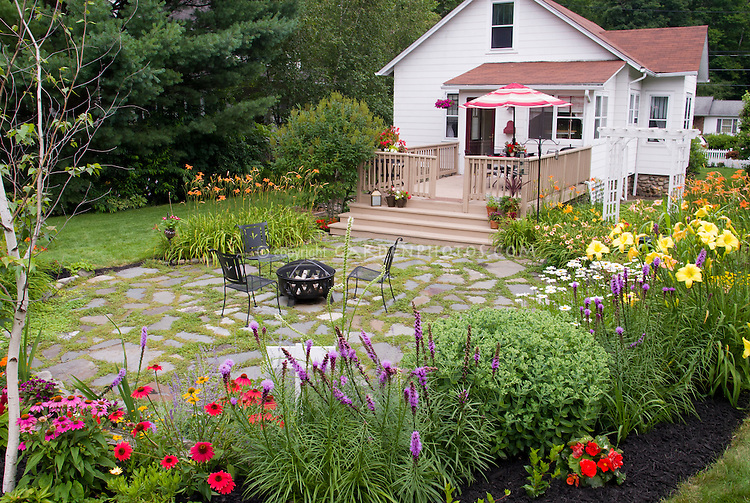 Mulched garden bed, Begonias, Liatris, Echinacea, Sedum, mixed annuals and perennials, patio, firepit and chairs, hemerocallis daylileis, deck with container garden pots, umbrella and house, lawn grass, landscaping in the backyard with flowers