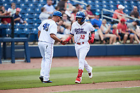 Jose Rodriguez (12) of the Kannapolis Cannon Ballers shakes hands with third base coach Guillermo Quiroz (40) after hitting a home run against the Carolina Mudcats at Atrium Health Ballpark on June 13, 2021 in Kannapolis, North Carolina. (Brian Westerholt/Four Seam Images)
