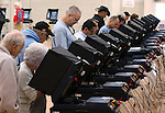 Election officials report a steady turnout of voters in Carson City, Nev., on Tuesday, Nov. 4, 2014. (AP Photo/Cathleen Allison)