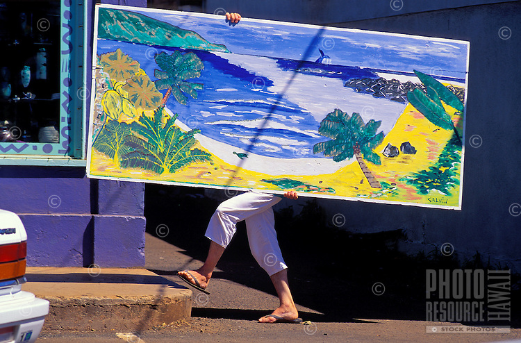 An artist carries a painting on a sidewalk in Paia town.
