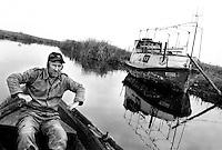 - Delta del Danubio, Laguna di Sacalin, Un pescatore lungo uno dei canali della laguna costretto a spingere la barca a remi per evitare che le eliche del motore si incaglino sul fondo causa del forte abbassamento del livello delle acque avvenuto nel corso degli ultimi anni..- Danube Delta Area, Sacalinu Lagoon. During the last years the water level of Sacalinu Lagoon went down considerably. That often forced Niku and the other fishermen to cruise by oars to avoid the enigine's propellers getting stuck in the canals' seaweeds.