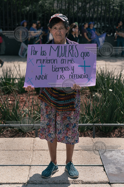 Josefina Rodriguez (80) holds a sign beside the Monument to the Revolution before a protest on Women's Day. ''I feel happy and sad to be here because there are many people who are very sore from losing their family, their children and their grandchildren.'' ''The situation right now is definitely ugly, in my time there was violence, but there were not so many things. Right now everything is lost.''