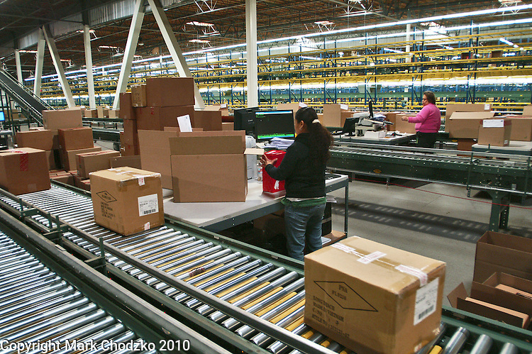 Interior large warehouse with freight on conveyor belts and women loading cartons and boxes.