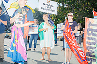 People stand at attention with pro-Trump flags and anti-vaccine signs while the national anthem is performed as alt-right organization Super Happy Fun America demonstrates against facemasks, vaccines, and pandemic closures, and in support of the reelection of President Donald J. Trump near the residence of Massachusetts governor Charlie Baker in Swampscott, Massachusetts, on Sat., Sept. 26, 2020. Super Happy Fun America is most well known for organizing the Straight Pride Parade in Boston on August 31, 2019.