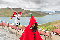 Tourists stand on a viewing platform overlooking Yamdrok Lake in Tibet. Nestled in at over 4,400m above sea level, the turqoise freshwater lake glistens, surrounded by rolling grasslands and snow-capped mountains.