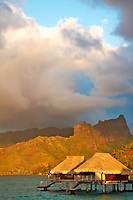 Golden light on Mount Tohivea and on overwater bungalows on Mooera island, a honeymoon destination near Tahiti, French Polynesia, Pacific Ocean