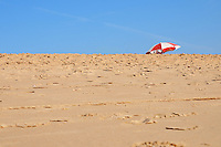 Sand beach close-up with colorful parasol on background over the blue skies